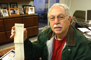 Terry Kastanis holds an original running tape of contribution amounts collected for the construction of the East Sacramento church. (Photo by Lance Armstrong)
