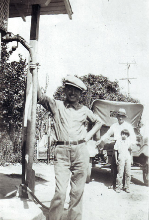 "Alfred Enos poses at a gasoline pump in the late 1920s at the Frank Enos Service Station. In the background stand Jake Buckley and Evelyn ""Toodie"" Lewis, near what is most likely Buckley's automobile. (Photo courtesy of PHCS)"