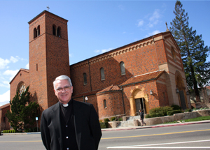 Monsignor Robert P. Walton stands in front of the Sacred Heart Church at 39th and J streets, where he has served as the church's pastor since 2002. (Photo by Lance Armstrong)
