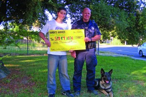 """Bandit's Buddies"" successfully raised $1,000 for two cooling units and a fan for the K9s who protect and serve the community with their human partners. Otto Ducey, left, presents a check to Sacramento Police Officer Gary Dahl and Bandit, his German Shepherd K9 partner. Bandit survived being shot in the line of duty earlier this year. Future fundraisers may go to purchasing Kevlar vests for K9s. / Valley Community Newspapers photo by Celia Green"