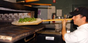 "A ""Pizza Rustica"" is lovingly placed into the oven to bake to delicious perfection by John Ruffaine, the ""Giovanni"" of Giovanni's Pizza. / Valley Community Newspapers photo, Tom Paniagua"