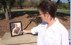 Tracy Kerth, recreation services manager of the Carmichael Recreation and Park District, observes a photograph of the wall's newest inductee, Lt. j.g. David A. Warne. / Valley Community Newspapers photo, Lance Armstrong