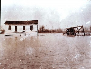The Edwards Break flood of 1904 damaged many houses in the Riverside-Pocket area, including the home of Manuel Perry, shown above. To the right of the house is a toppled, wood-frame tower. / Photo courtesy of PHCS