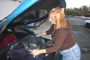 Jan Wilson places a bag filled with donated clothing and blankets in the back of the car that she uses to transport these and other donated items to people in need. / Valley Community Newspapers photo, Lance Armstrong