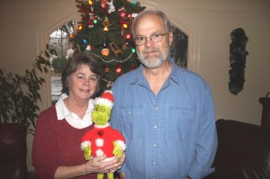Gary and Missy Stonehouse stand with a plush Grinch doll in front of their Christmas tree in their Land Park home. The couple has been celebrating the annual holiday in their home since 1972. / Valley Community Newspapers photo, Lance Armstrong