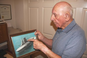"P.R. ""Tony"" Tonelli points to a photograph of the USS Saratoga, the aircraft carrier that he served on for more than two years during World War II. Tonelli described the vessel, which carried about 4,000 workers, as a ""city onto itself."" / Valley Community Newspapers photo, Lance Armstrong"