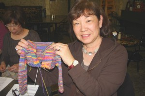 Sandy Nishimura-Yee shows off one of her latest knitting projects, a small child's jacket. / Valley Community Newspapers photo, Lance Armstrong