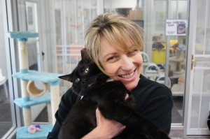 "Cathryn Reynolds cuddles one of the cats that is available for adoption to a ""fur-ever home"" at Happy Tails Pet Sanctuary in East Sacramento. / Valley Community Newspapers photo, Ellen Cochrane"