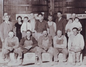 "Silva Bros. Winery workers and others gather together in this late 1920s photograph. Back row, from left to right: Manuel Ignacio Silva, Mary Silva, Norman Silva (son of King), King Silva, John Mendonca, unidentified worker, bookkeeper Manuel Lucas and Sergio ""Sam"" Silva holding his twin daughters, Lillian and Lorraine Silva. Front row, sitting on Silva Bros. Grape Syrup boxes: Only Tony Silva and William Santos, second and third from left are identified. / Photo courtesy, PHCS"