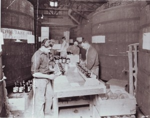 Silva Bros. Winery workers prepare bottled grape syrup for shipping during the late 1920s. King Silva is shown in the foreground to the right and John Mendonca is shown in the foreground to the left. / Photo courtesy, PHCS