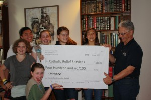 Girl Scout Troop 762 is working to raise $1,000 to help relieve the suffering in Japan after the devastation of Japan's recent earthquakes and tsunami last March. Here, they present their first check to Joseph Symkowyk of Catholic Relief Services. / Photo courtesy, Girl Scout Troop 762