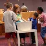CHILDREN from Faith Presbyterian Church emptied bottles of water into a tub in front of the altar at Faith Presbyterian. The water sybolized the new life fresh water provides. / Photo courtesy, Barbara Tracy