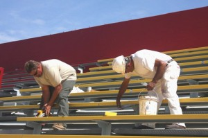 Bill Hall and Naealio Torres of Moorfield Construction work on new seating on the east end of Hughes Stadium. / Valley Community Newspapers photo, Lance Armstrong