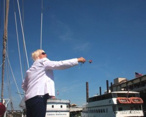 Brenda Payne tosses a red rose toward the water while standing aboard the pirate ship-themed yacht, Sea Eagle. / Valley Community Newspapers photo, Lance Armstrong