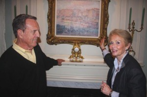 LOCAL ART SHOW. With her husband, John Reid, Carolyn Reid presents one of her favorite paintings during a home tour preview of her residence. / Valley Community Newspapers photo, Lance Armstrong