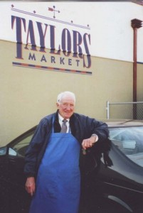 Ed Schell stands in front of Taylor's Market, where he has continuously worked since 1962. / Photo courtesy, Ed and Colleen Schell
