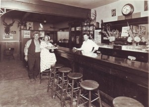 Manuel J. Viera, Sr. stands behind the bar in his Southside Park area business, Viera's Place, in this c. 1940 photograph. The people to the left of the photograph are unidentified. / Photo courtesy, Mannie Viera