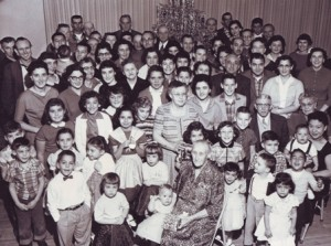 CHRISTMAS PAST. Mary Nevis, lower, center with a Christmas present in her hands, is shown in this 1957 photograph at the age of 80 with more than 80 members of her family. Mary was the wife of Manuel Nevis, Sr. / Photo courtesy, Sacramento Portuguese Cultural and Historical Society