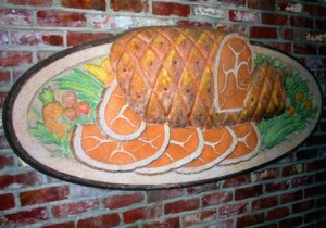 ARTWORK. This image of a ham on a platter is among the various food-related artworks on the exterior of the restaurant building. / Valley Community Newspapers photo, Lance Armstrong