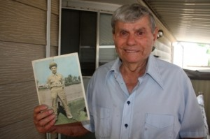 JOHN KANELOS, former Land Park resident of 15 years, shows off a photograph of himself from his war days in 1943. / Valley Community Newspapers photo, Lance Arms