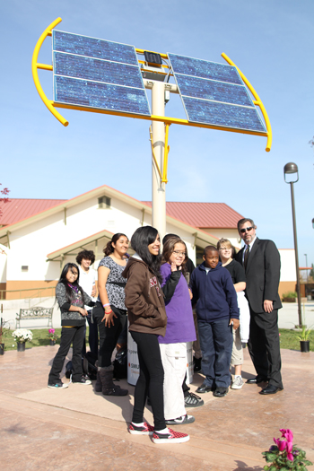 Students of the School of Engineering and Science stand in front of the school's new Solar SunFlower, an 18-foot-high outdoor learning lab. Students can rotate the panels to see how much electricity the sun provides and study changes in the voltage and current being generated. / Photo courtesy