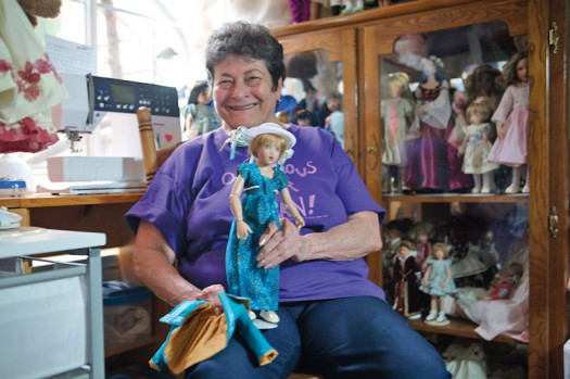 Photo of Jean Siler and her collection of dolls, wearing clothing she made for them. / Photos by Sally King