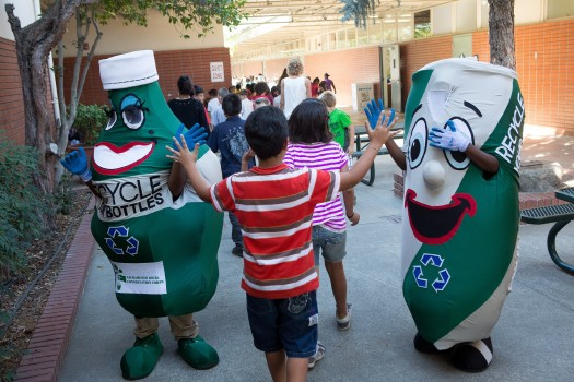 Student greets recycling mascots at Whitney Avenue Elementary in Arden Arcade. Betty Bottle and Al Luminum from the California Conservation Corps entertained Whitney Avenue Elementary students during the official launch of Read, Write, Recycle!, a recycling contest for students of San Juan and Natomas Unified School Districts. / Photo courtesy of Timothy Douglas
