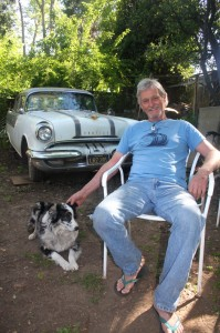 Hugh Gorman relaxes with his dog behind his art studio. Photo by Lance Armstrong