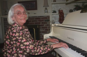 Betty Kline sits at her ivory Yamaha piano, which she purchased from a music dealer in Placerville. Although she founded Kline Music, Betty does not consider herself a musician. Photo by Lance Armstrong