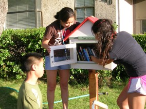 (From left) Jonathan Louie, Allison Yamamoto, and JasMin Khoe install the first Bound Together Library. Photo courtesy Kathi Windheim