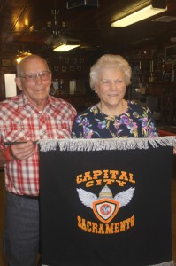 Merrill Wolhart and his wife, Lee, hold a banner featuring the club's colors. Merrill joined the club in 1951, and also attended the club's 50th anniversary. Photo by Lance Armstrong