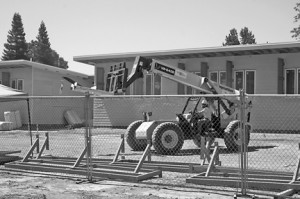 A forklift driver maneuvers his vehicle on the east side of the school construction site. Photo by Lance Armstrong