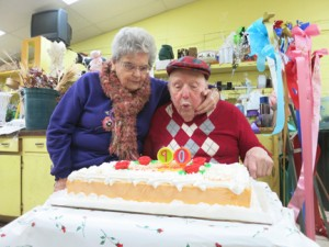 While sitting alongside his wife, Marie, Al Balshor blows out candles on his birthday cake during a gathering in his honor at Balshor Florist on Nov. 22, 2014. Photo by Lance Armstrong