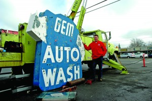 Gem Auto Wash owner Reed Hollingshead poses with the old Gem Auto Wash sign. / Photo by Greg Brown