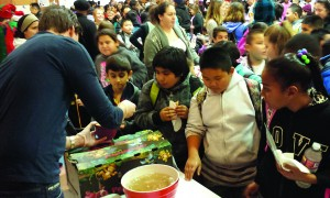 Rick Verduin serving pomegranate seeds to Castori Elementary School students. /Photo by Anthony Catafi