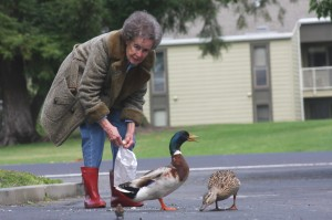 "Dolores Greenslate feeds ducks in the Pocket area. Greenslate, who was once known as the ""Duck Lady,"" is shown in some of her original duck feeding attire, including boots that she wore while feeding ducks at Lake Greenhaven during the 1960s. Photo by Lance Armstrong"